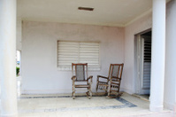 Two old wooden chairs on the porch