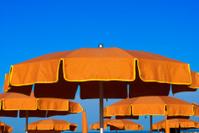 Orange umbrellas on blue sky