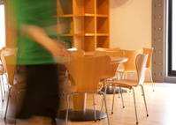 Woman Walking Near Tables and Chairs