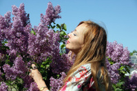 Pretty young woman in the garden among lilacs