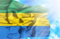 Gabon waving flag against blue sky with sunrays