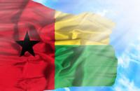 Guinea Bissau waving flag against blue sky with sunrays
