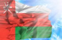 Oman waving flag against blue sky with sunrays