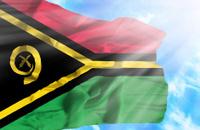 Vanuatu waving flag against blue sky with sunrays