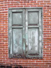 Brown wooden window on brick wall
