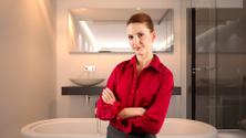 Businesswoman of a Realtor in a Model Bathroom