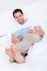 Portrait Of Young Man Reading Book On Bed
