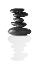 Tower of five balancing smooth black pebbles