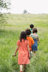 Children Walking On Grassy Field