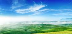 Misty sunrise over green fields of Tuscany