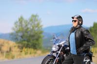 Mature biker walking in front of his motorbike
