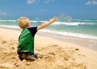 Boy Playing on a Sandy Beach Throwing Sand