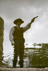 Reflection of a Cowboy with Gun in Pond Ripples