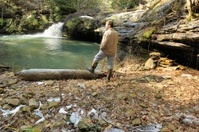 Man hiking and enjoying scenic waterfall