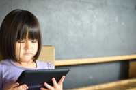 little girl looking at an electronic device