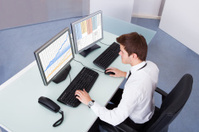 Stock Broker Using Computer At Desk