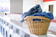 Basket of Laundry Sitting onto of Washers at the Laundromat