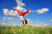 Girl doing Cartwheel on meadow