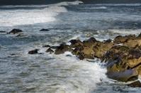 Big waves crashing against the coastal rocks at night