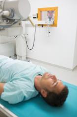 Female doctor behind window proceeding radiography
