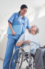 Elderly patient in a wheelchair next to nurse