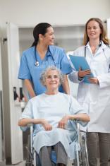 Nurse wheeling patient in a hallway
