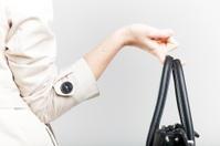 Elegant woman holding on finger black bag, back view