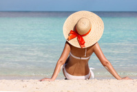 Sexy girl on tropical beach. Vacation. Woman in Sun Hat