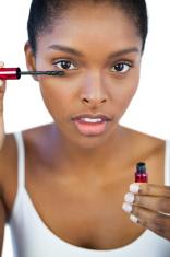 Serious brunette using mascara for her eyelashes
