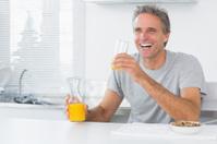 Happy man having orange juice with breakfast