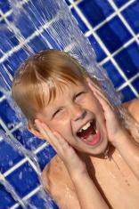 Boy under a pool waterfall