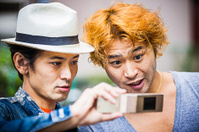 Two Japanese geeks looking at mobile phone