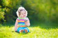 Happy toddler girl eating ice cream in a garden