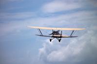 Biplane Flies Toward Clouds in Distance
