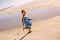 Smiling girl running at beach