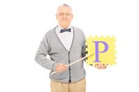 Mature teacher holding a piece of puzzle
