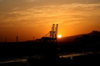 Shipping dock crane sunset.