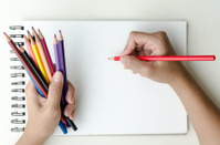 Man holding colored pencils and sketching