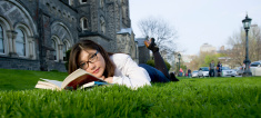 young female student reading textbook outside in grass