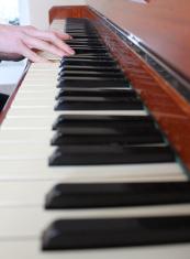 Image of teenage boy playing the piano, wooden piano keyboard