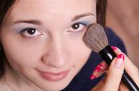 Makeup artist applies powder on face of beautiful girl
