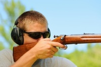 Close up of young man aiming wooden rifle