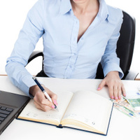 Businesswoman writing in organizer