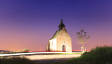 Chapel at dusk crossed by car lights