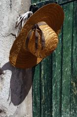 Stylish straw hat on the wall