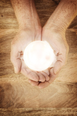 Glowing Crystal Ball in Mature Hands on Wood Background