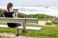 Woman using an electronic tablet on a bench