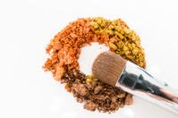 Crushed eyeshadow and professional make-up brush isolated on whi