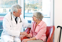 Friendly doctor reassuring an elderly woman.