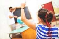 adult teacher at the classroom blackboard teaching